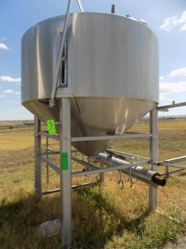 Aprox. 5,000 L / 1,320 Gal. Cone-Bottom S/S Tank with Heated Cone-Bottom, Wide Outlet, Man Hole, Pressure Relief Valve, Hot Water Connections and 4-Leg S/S Base (Previously Utilized for Cheese)