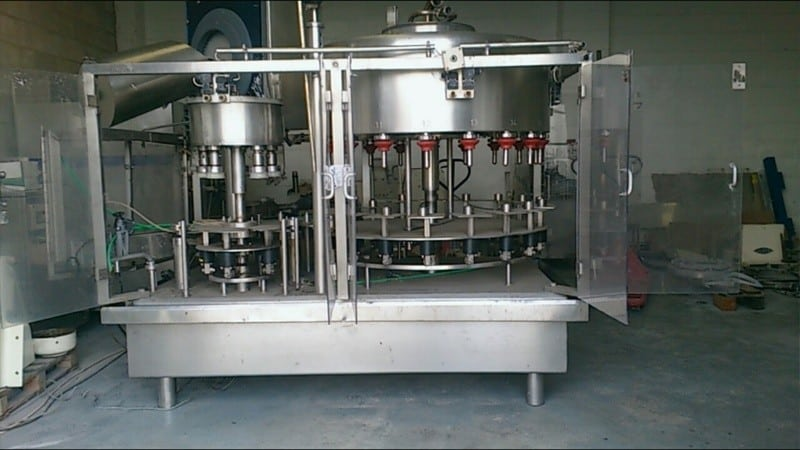 Filmatic 18-Valve Mono-Block Filler with 6-Head Rotary Cap Snap Capper, Cap Sorter, Utilizes 38 mm Cap Size, Safety Switches, CIP Ring, Product Valve Inlet, Fully Guarded Cabinet, Set-Up with 1 Litre Change Parts