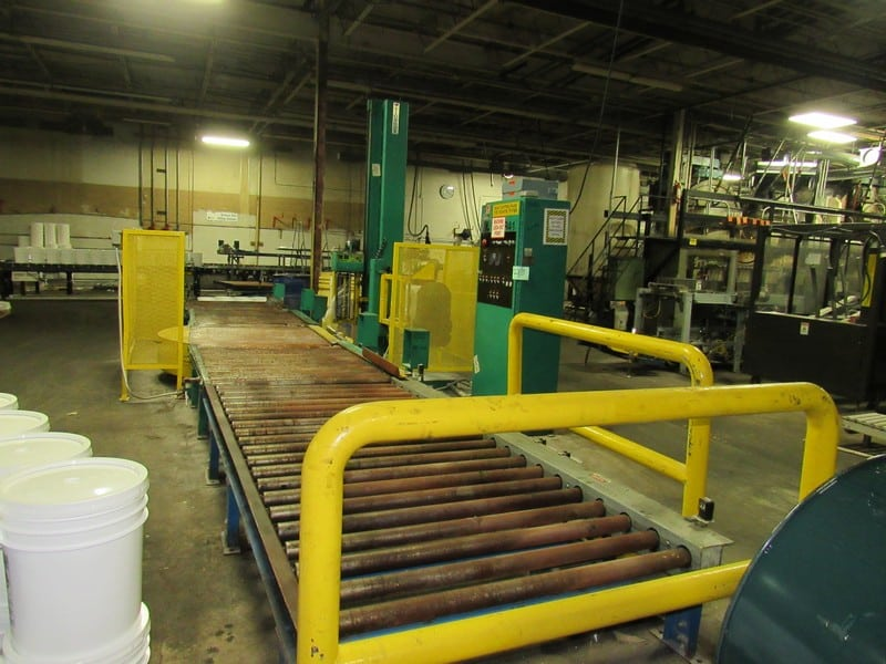 Signoid Automatic Stretch Wrapper with 10 ft infeed and about 15 ft outfeed roller conveyor, currently in operation