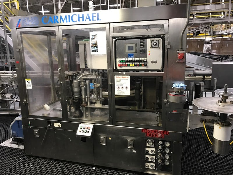 KHS Carmichael Model 920B Roll Fed Labeler, S/N: 2412-B5-0034-SP-CW, Dual unwind station, S/S frame, Nordson Glue Unit, Allen Bradley PLC Controlled, Change Parts for .5L 20oz and 24oz PET Bottles, Dims: 12' L x 9' W x 8' H, Speed: 400+ BPM, Electricity: 460V 3PH 60HZ