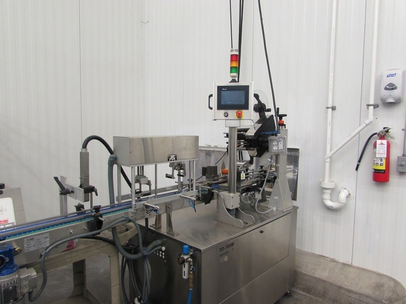 2017 Tadbik Pressure Sensitive Labeler, Model TD 700M, S/N 2962, Full Wrap Around Labeler with Large Die Cut Label Applied to Top with Side Wipers and Front and Back Wipers to Complete Label on Top and all 4 Sides, Previously Operating on 2017 Action Pak and Pack Line Cup Filling Line , Over $62,000 Cost in 2017 (Asset No. 40-000511)(SUBJECT TO BULK BID IN LOT 20)